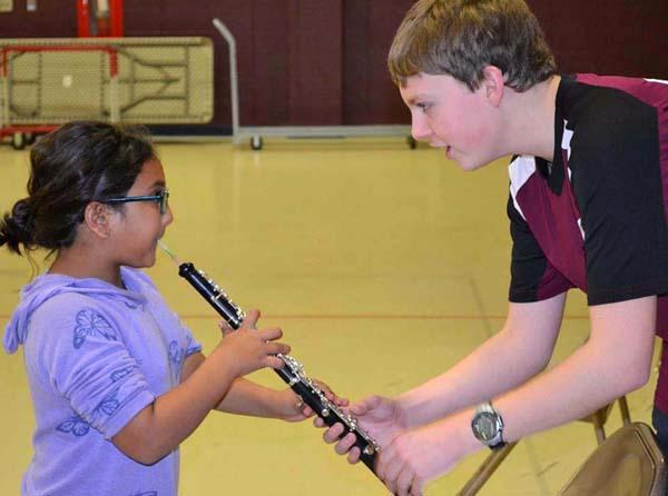 CHS students assisting WIS student with Oboe